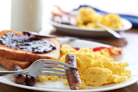 sausage links being pick up by a fork at a big breakfast  photo