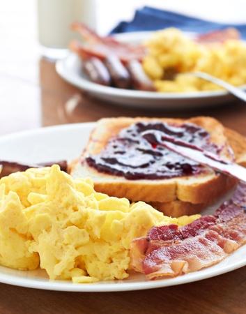 desayuno con huevos revueltos y bacon con tostadas con mermelada Foto de archivo