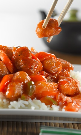 sweet and sour: sweet and sour pork on rice being eaton with chopsticks