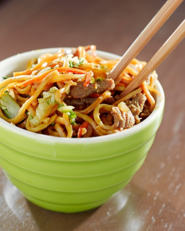 eating noodles: beef lo mein in a bowl with chopsticks