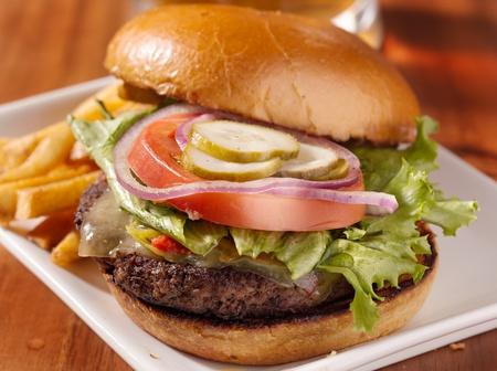papas fritas: gourmet hamburguesa con queso y jarra de cerveza en el fondo Foto de archivo