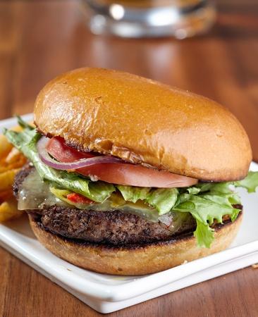 gourmet cheeseburger with mug of beer in background