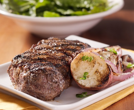 new york strip: steak dinner with potatoes and salad in background Stock Photo