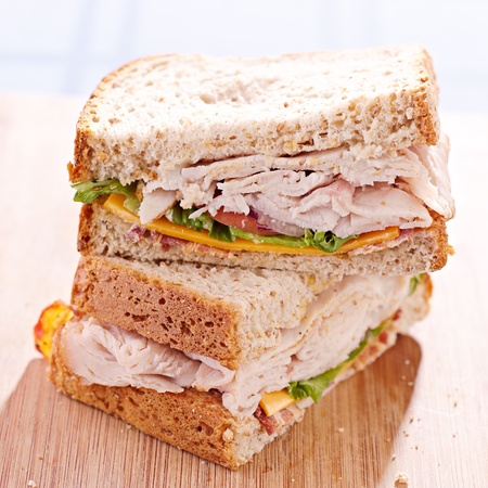 a turkey club sandwhich cut in halves with selective focus