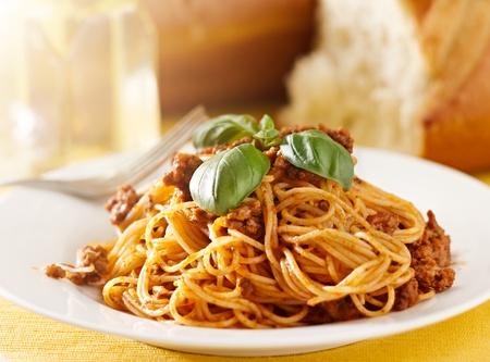 spaghetti with basil garnish in meat sauce Stock Photo