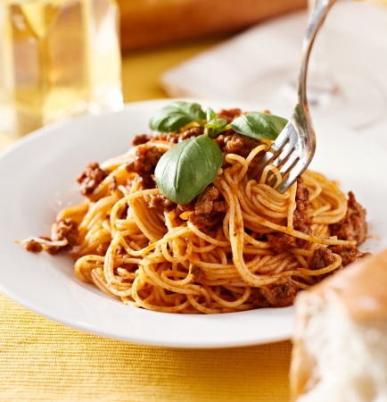 bolognese: spaghetti with basil garnish in meat sauce Stock Photo