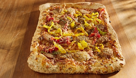 rectangular gourmet pizza with sausage and colorful peppers