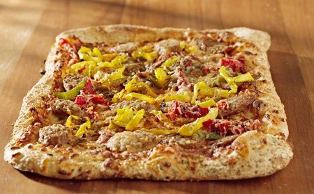rectangular gourmet pizza with sausage and colorful peppers photo