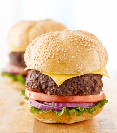 Two cheeseburgers on a wooden surface. photo