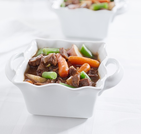 beef stew with potatoes, carrots, and greenbeans on a white tablecloth.