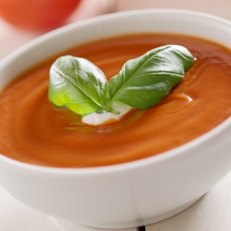 tomatensoep met basilicum garnering. Stockfoto