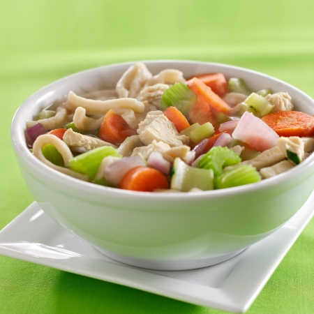 vegetable soup: bowl of chicken noodle soup with copyspace composition