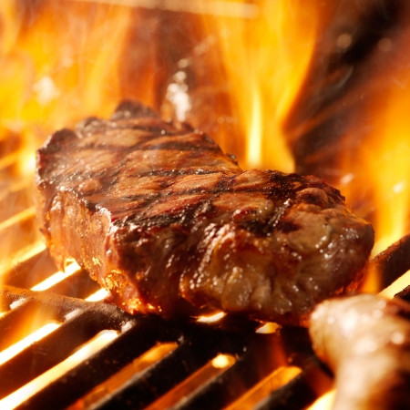 grill food: beef steak on the grill with flames.