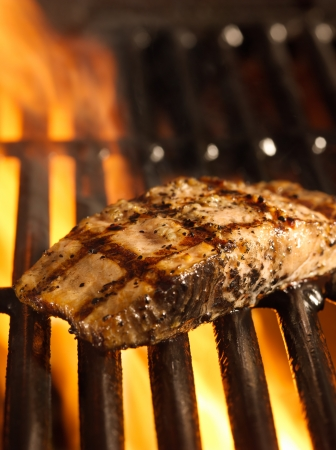 grilled salmon: salmon fillet on the grill with flames