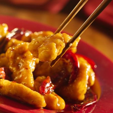 Comida chinesa - Comer frango do general tso com pauzinhos. Banco de Imagens