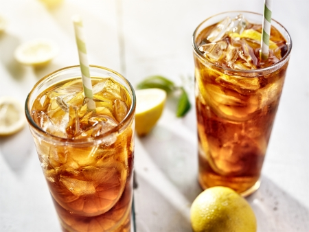cold iced tea with straws and lemon slices in summer sun. Stock Photo