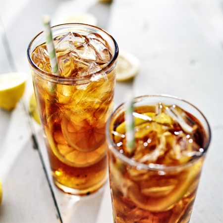 ice lemon tea: two cold iced tea with straws and lemon slices. Stock Photo