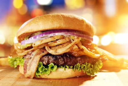 gourmet burger: Gourmet hamburger with fried onion straws and cityscape background.