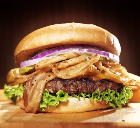 large gourmet hamburger with fried onion straws.