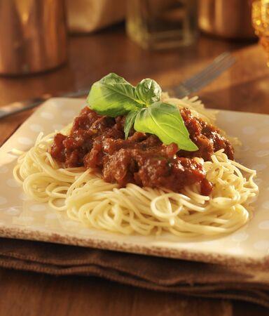 Spaghetti with basil garnish and tomato sauce.