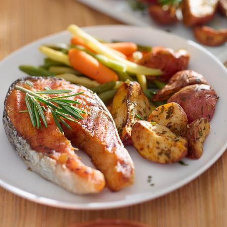 salmon dinner: Salmon steak dinner with herbs and roasted potatoes. Stock Photo