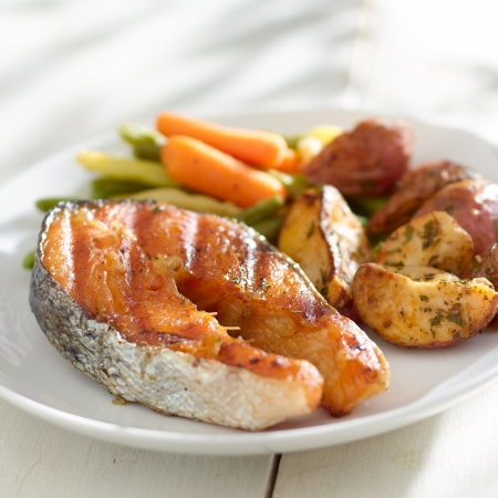 grilled fish: Salmon steak dinner with herbs and roasted potatoes. Stock Photo