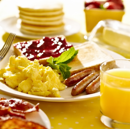 scrambled eggs: desayuno con huevos revueltos, salchichas y tostadas.