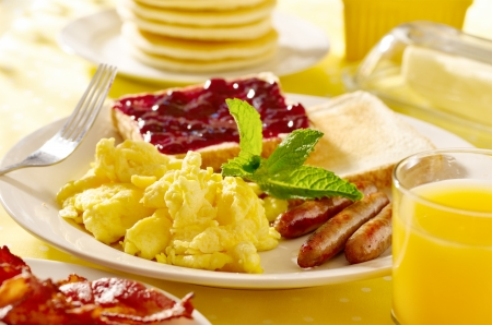 breakfast with scrambled eggs, sausage links and toast. Banco de Imagens