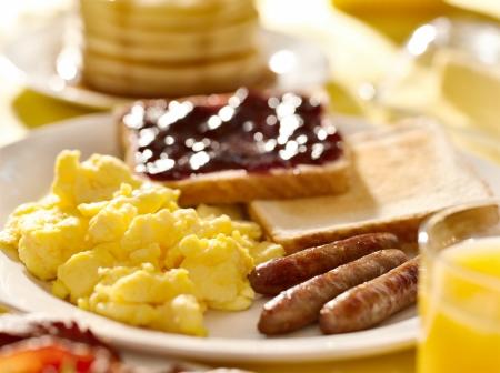 desayuno con huevos revueltos, salchichas y tostadas. Foto de archivo