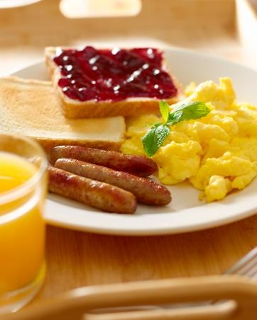 huevos revueltos: comida del desayuno - el desayuno estilo americano con huevos revueltos, salchichas y tostadas.
