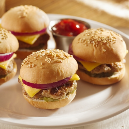 sliders: mini burgers with cheese, onion and pickle  Stock Photo
