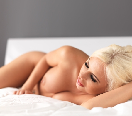 nude blonde laying on bed