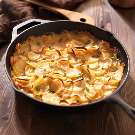 casserole dish: scalloped potatoes in rustic iron skillet Stock Photo