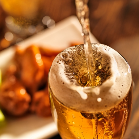bier glazen: gieten bier met kippenvleugeltjes in achtergrond.
