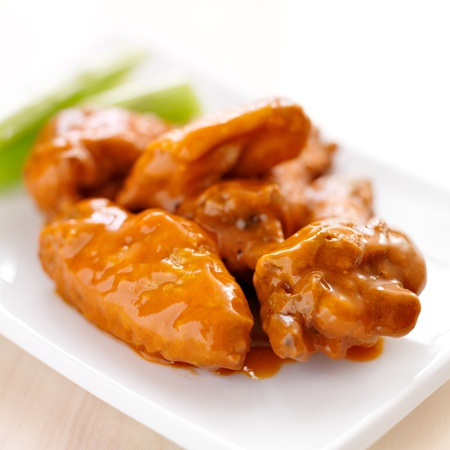 pub food: plate of buffalo wings with celery.