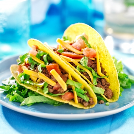 latin food: Mexican food - Hard shell tacos with beef, cheese, lettuce and tomatoes