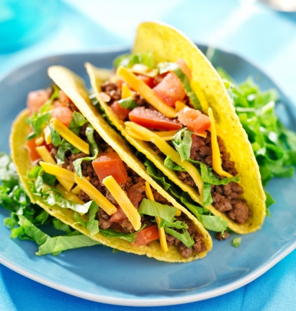 Mexican food - Hard shell tacos with beef, cheese, lettuce and tomatoes photo