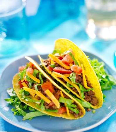 close up food: Mexican food - Hard shell tacos with beef, cheese, lettuce and tomatoes