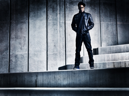 cool urban african american man on distopic concrete steps photo