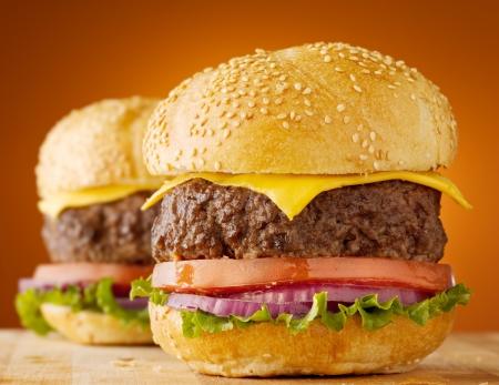 dva: cheeseburgery na dřevěné desce.