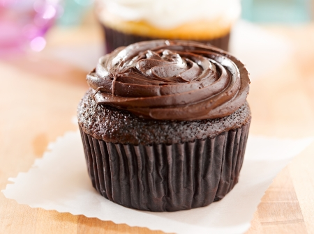 chocolate cupcake sitting on wax paper.