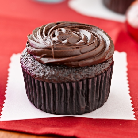 confectionary: chocolate cupcake sitting on wax paper.