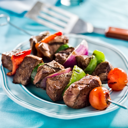 grilled beef shishkabobs on table 写真素材