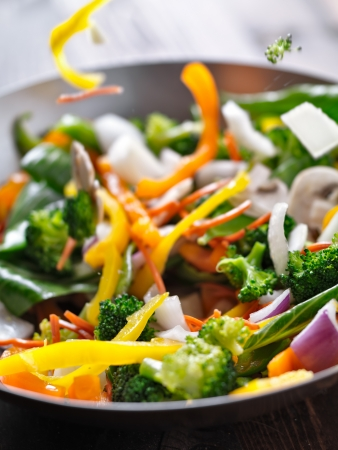 stir fry: vegetables falling into a stir fry wok