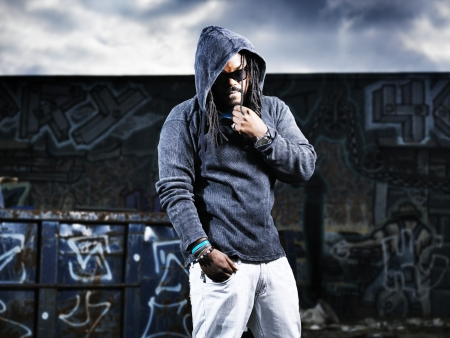 hoody: man in hoodie in front of graffiti
