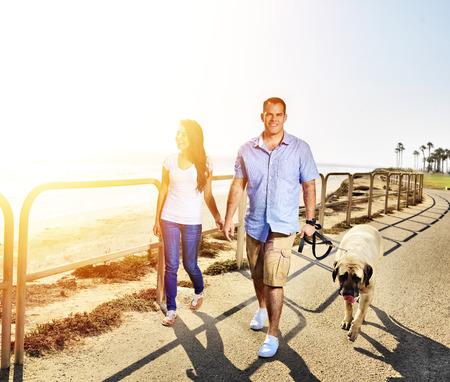 couple walking pet dog by the ocean photo
