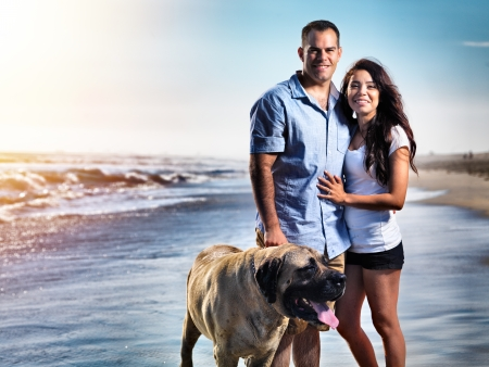 couple with pet dog posing on the beach. photo