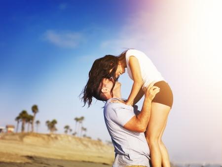 enamorados besandose: pareja romántica en el momento íntimo en la playa Foto de archivo