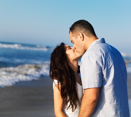 romantic couple kissing each other on the beach  photo