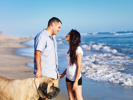 romantic couple on the beach with pet dog  photo